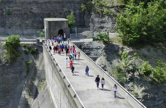 School children tour a dam facility, learning both about how water is managed and how hydroelectricity is generated